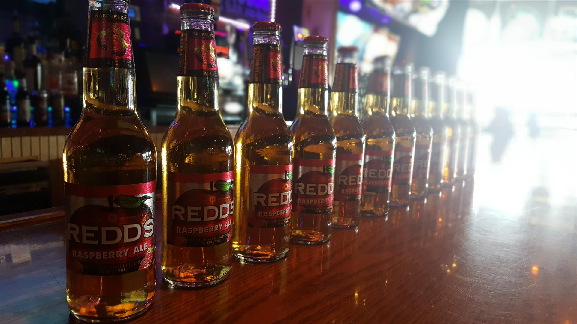 assortment of Redd's bottles on a bar top