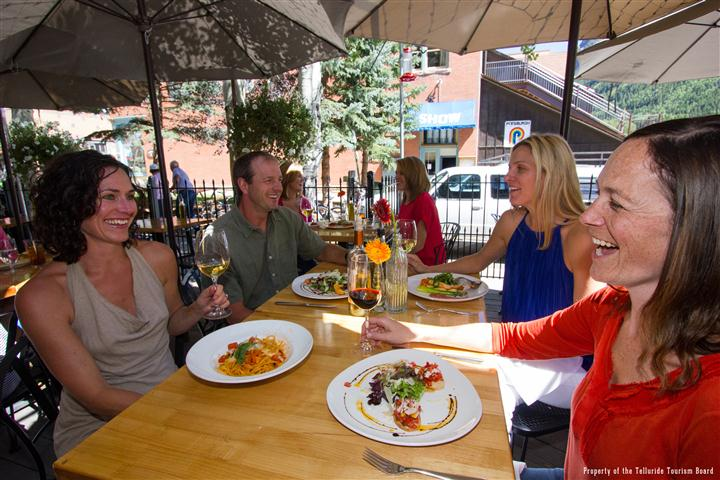 A group of people socializing and smiling at a dining outdoor patio