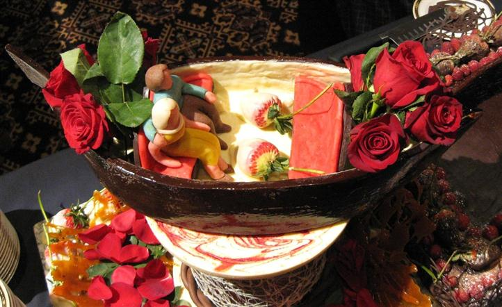 Decorative model of a couple sitting in a boat with strawberries and cream in it