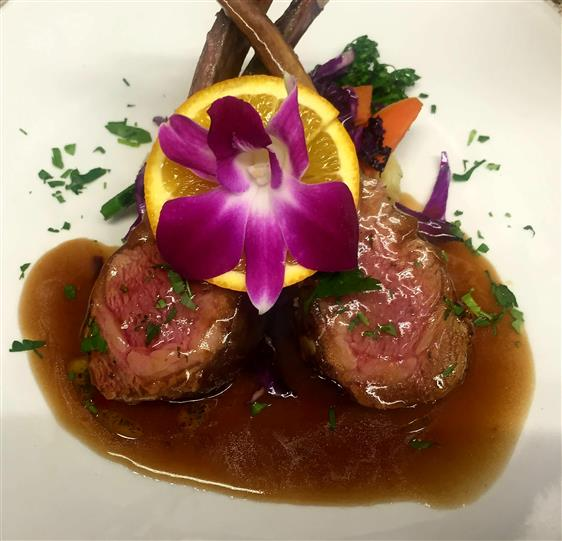 Lamb chops in gravy topped with a lemon and a flower