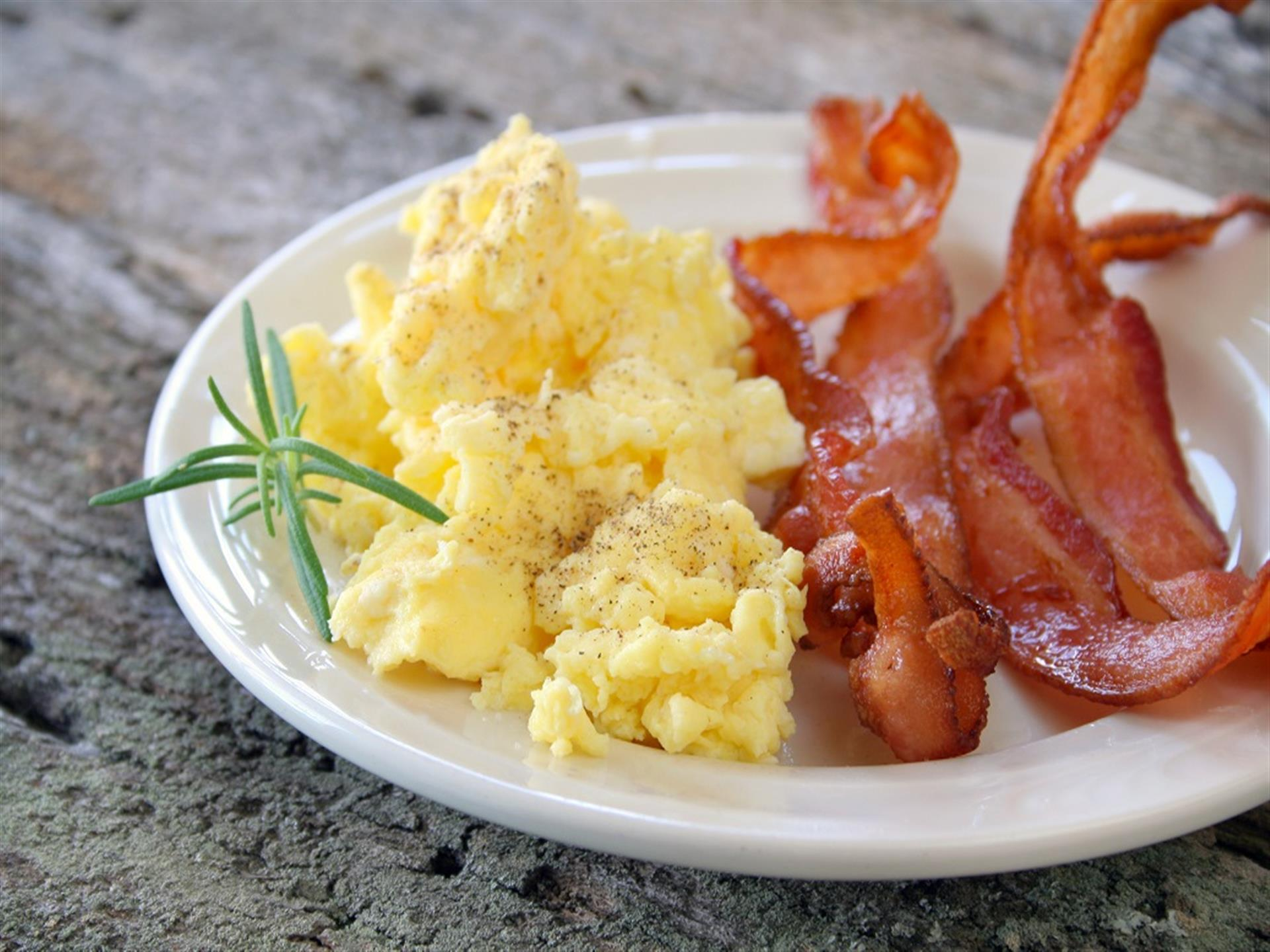 scrambled eggs and bacon on a plate