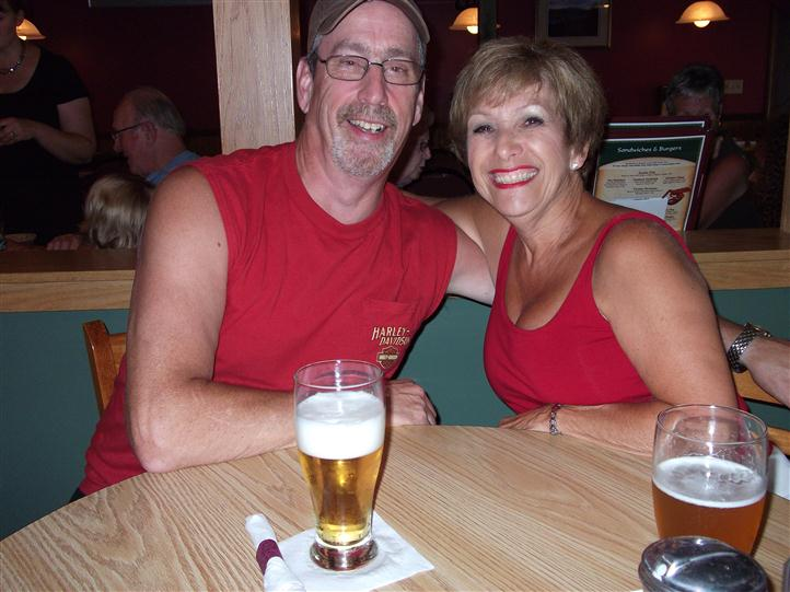 Couple posing for photo at the table with two glasses of beer on top