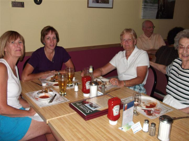 Group of people sitting at a table and posing for photo