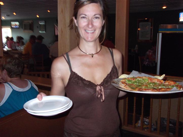Woman holding plates and a pizza and smiling for photo