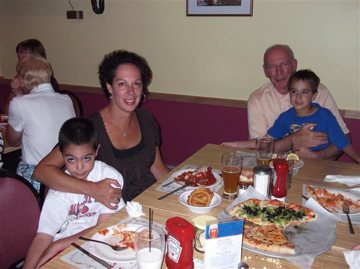 Family sitting at a table and posing for photo