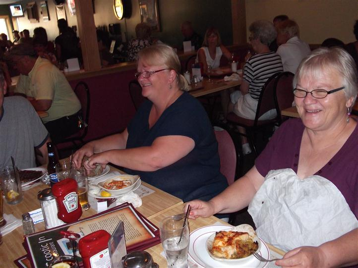Two women eating at the table and smiling for photo