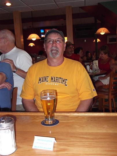 Man posing for photo with a glass of beer at the bar