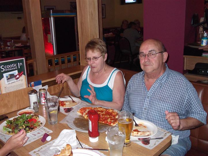 People having pizza and drinks at the table and posing for photo
