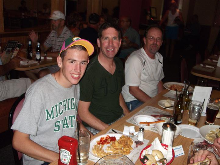 Men having dinner at the table and smiling for photo