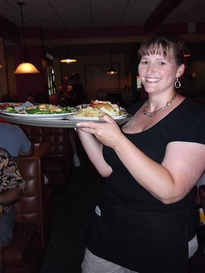 Woman holding a big tray of food smiling for photo