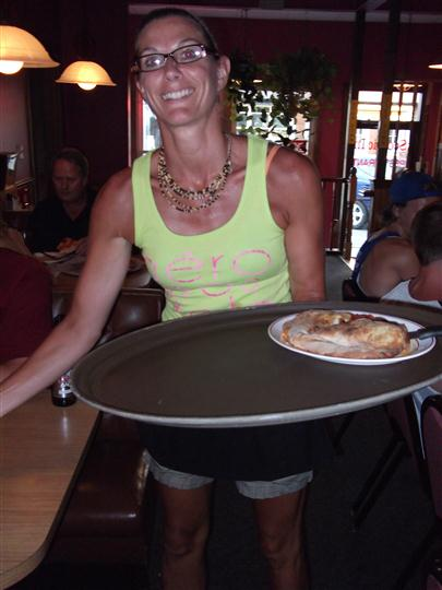 Woman serving food and smiling for photo