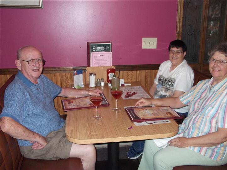 People sitting with the menus in front of them smiling for photo