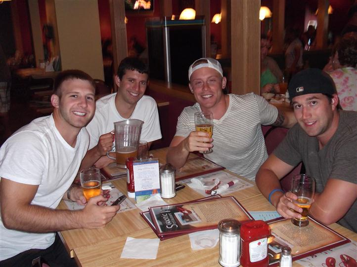Young men having beer at a table and posing for photo