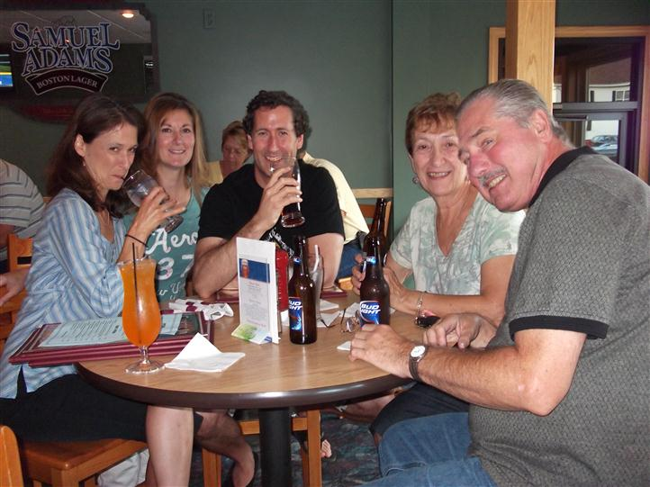 Group of people having drinks at a table and posing for photo