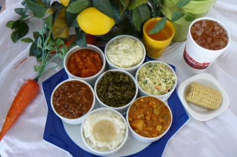 tray of side dishes, including baked beans, mashed potatoes, collard greens, and cole slaw