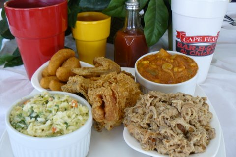 cole slaw, brunswick stew, fried chicken, hush puppies, and pulled pork on a table