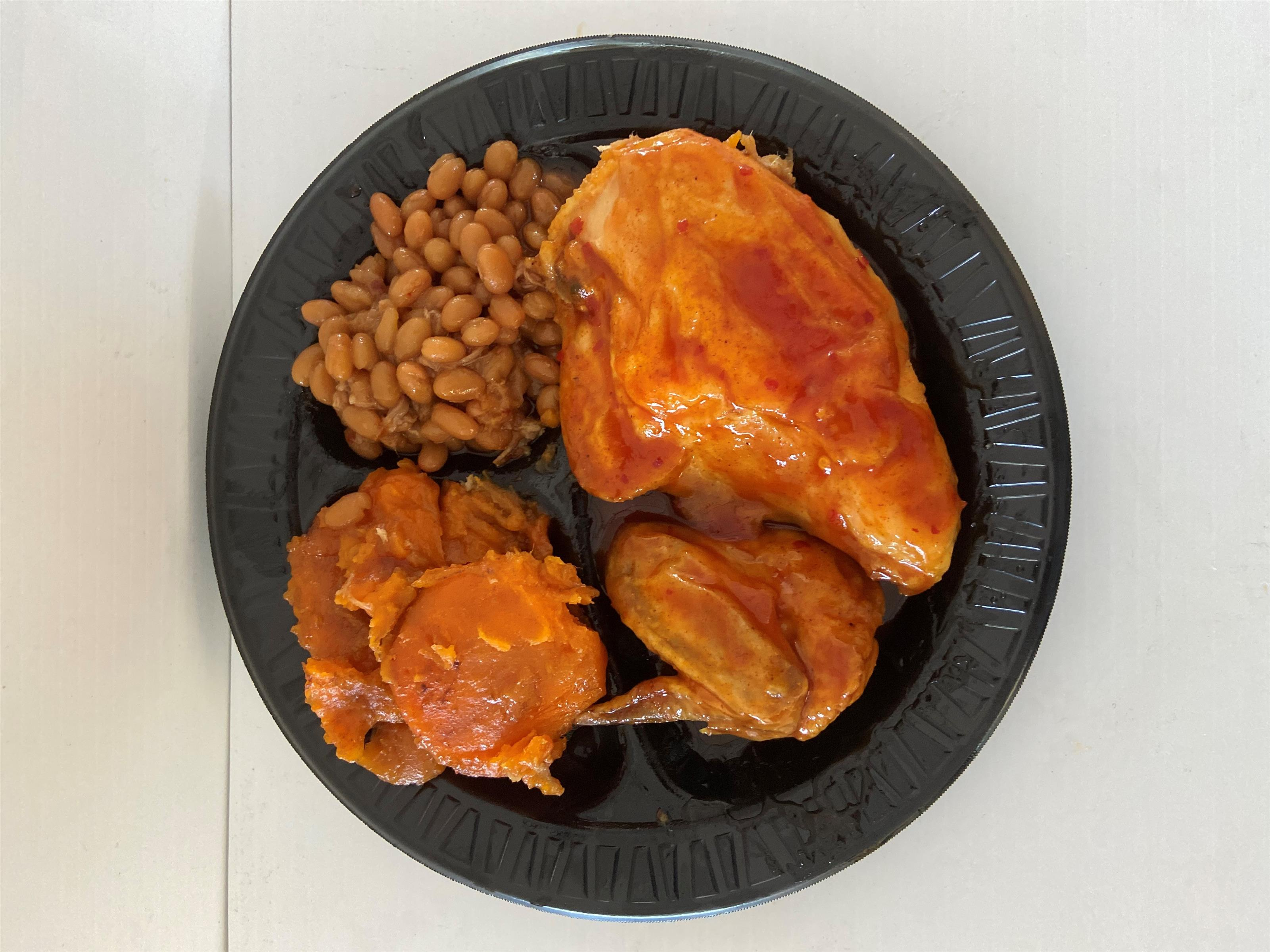 plate of pieces of BBQ chicken, mashed sweet potatoes and baked beans