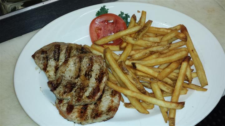 Grilled chicken served with a side of french fries, lettuce, and a tomato slice