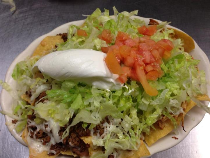large taco with meat, lettuce, tomatoes and sour cream