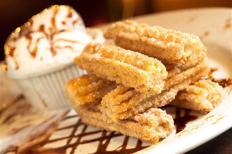 churros stacked together on a plate with a side of ice cream
