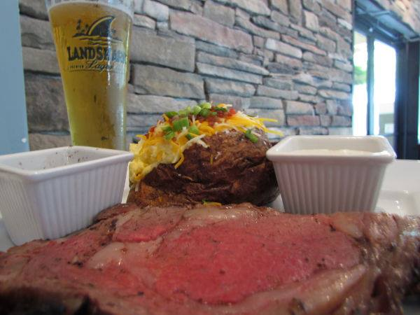 Rare steak with a side baked potato and a Landshark beer.