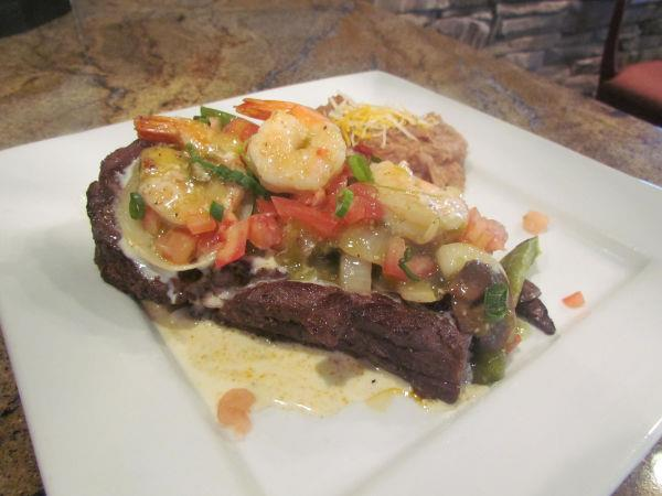 Steak topped with mixed vegetables and shrImp served with a side baked potato with cheddar.