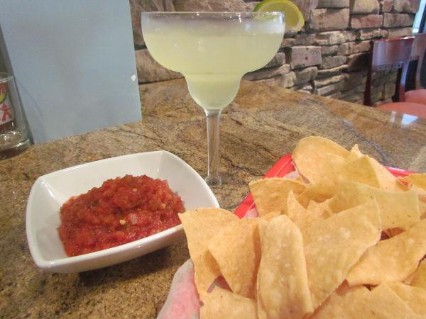 A margarita with a lime on a table top with a bowl of chips and salsa.