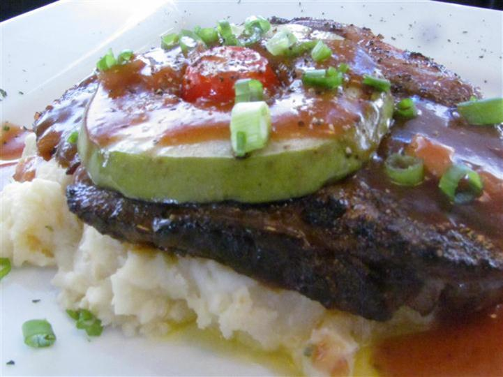 Red meat on top of mashed potato with scallions and a cherry tomato.