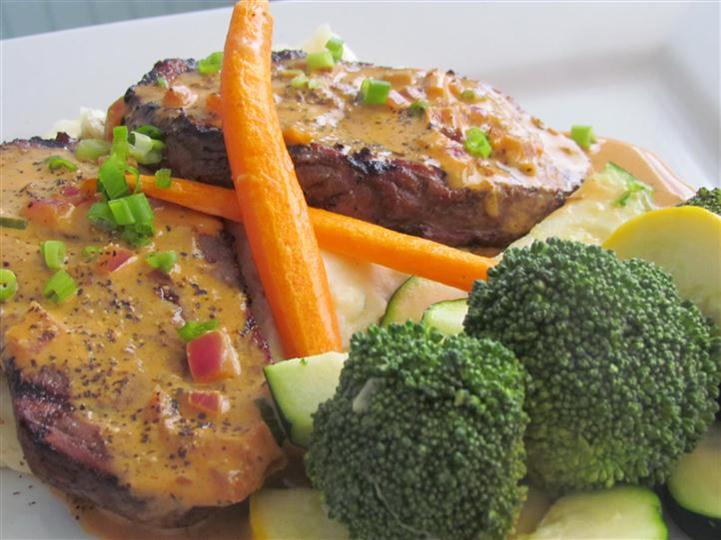 Red meat topped with medlted cheese, and scallions and served with a side of broccoli and carrots.