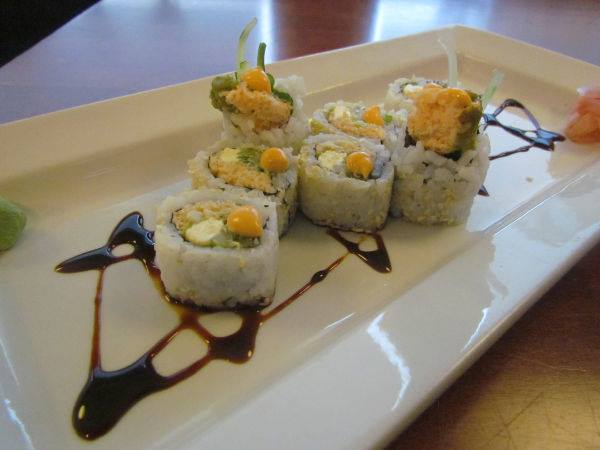 Sushi on a plate with soy sauce drizzle.