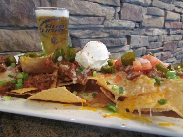 Nachos on a plate served with a pint of bud light.