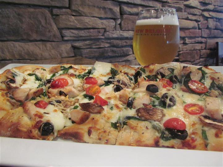 Flatbread pizza with tomato, spinach, mushroom and cherry tomato. Served with a beer.