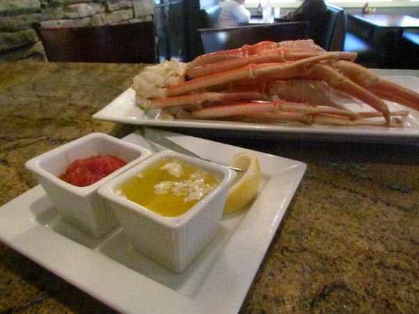 Crab legs on a plate with a side of butter and cocktail sauce.