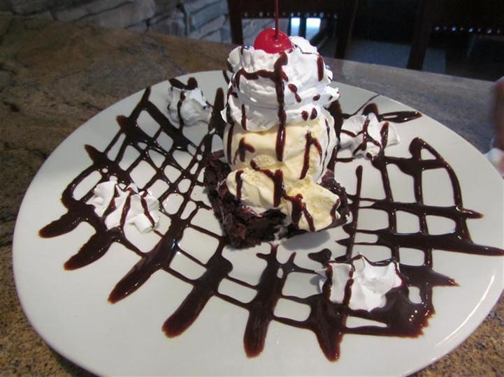 Scoop of vanilla ice cream served on top of a brownie with whipped cream and a cherry.