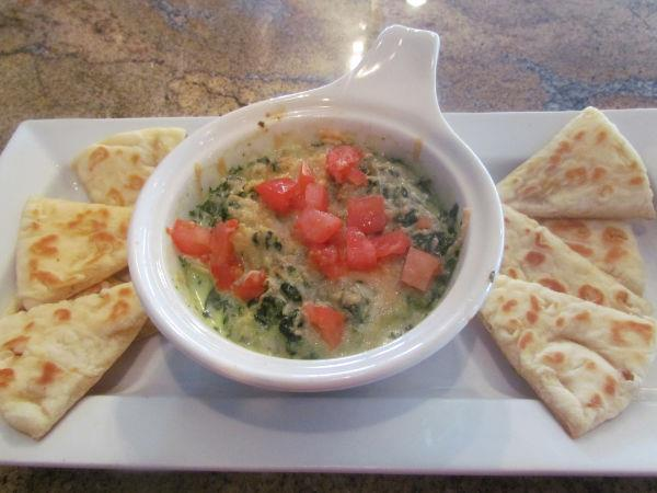 Spinach artichoke dip in a bowl topped with diced tomatoes and pita chips.