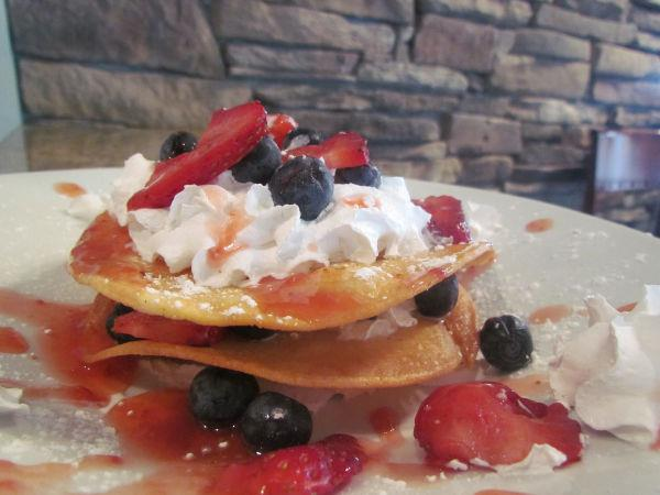 Thin pancakes with whipped cream, strawberries and blueberries.
