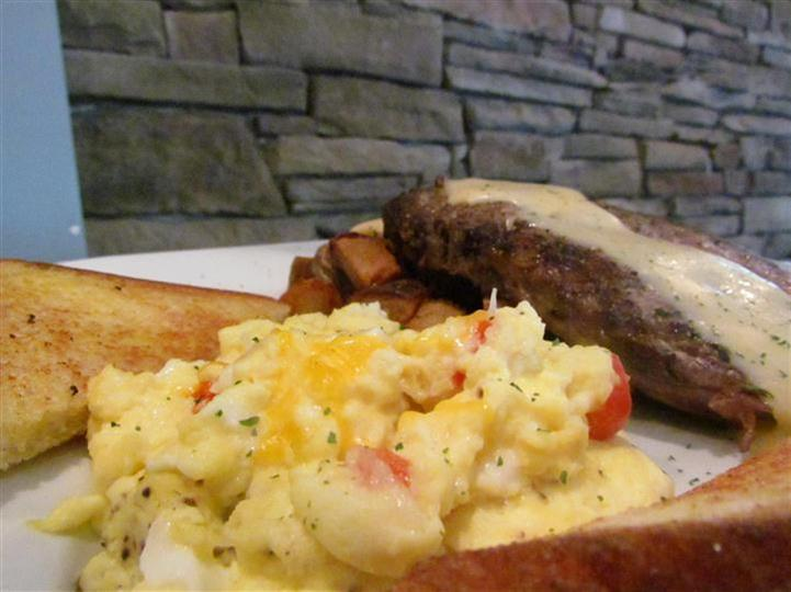 Scrambled eggs and steak on the side with toast.