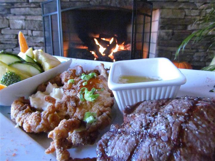 Steak and fried seafood entree served with a side of melted butter and mixed vegetables.