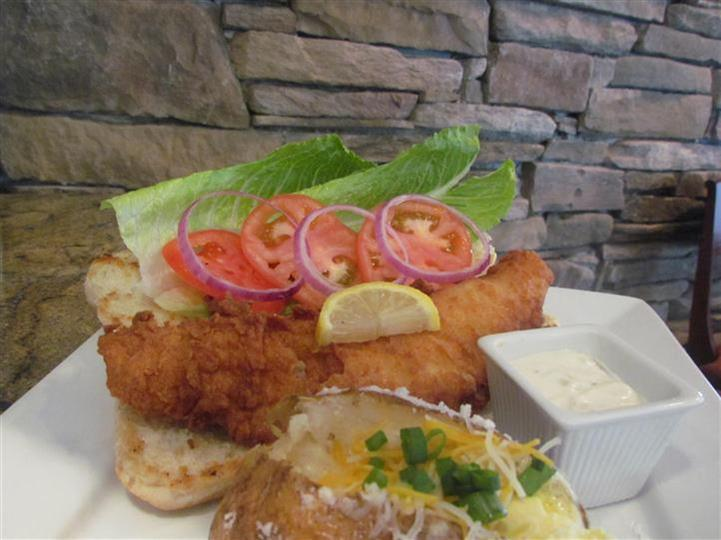 Fried fish on a sandwich open with lettuce, tomato and red onion and a lemon slice. Served with a side baked potato.