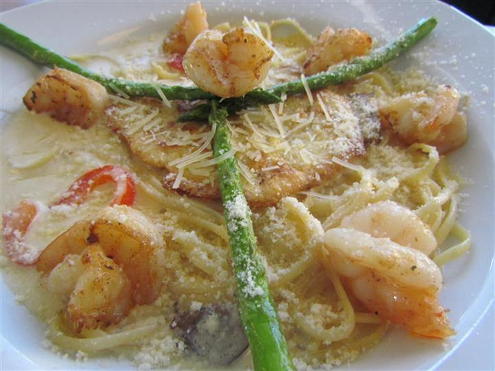 Breaded fish served with shrimp and scallops in a creamy sauce and a side of asparagus