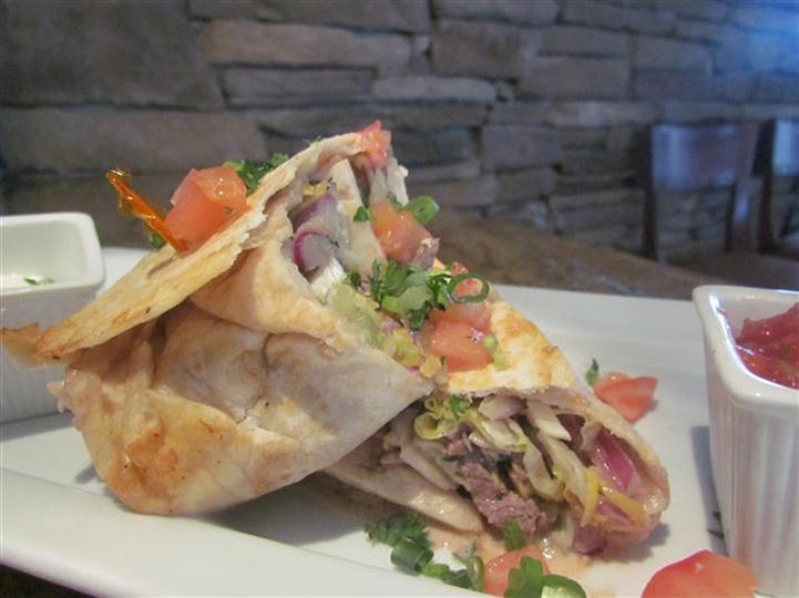 White wrap with diced tomato, red onion, scallions and red meat.