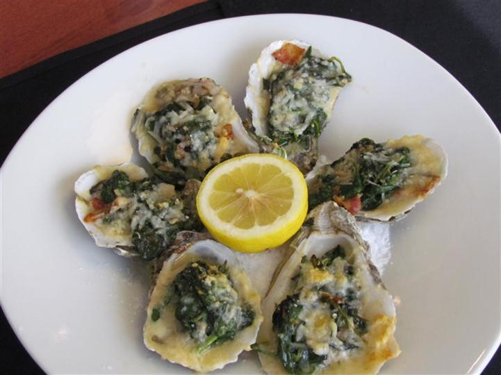 Five oysters on a white plate.