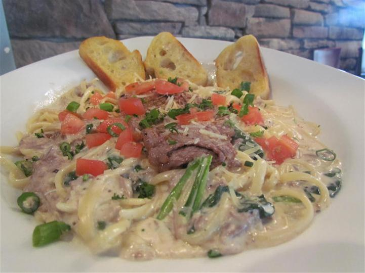 Linguini pasta in a cream sauce with diced tomato, scallions, and red meat.