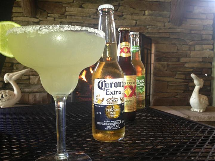 A maragarita on a table with a corona extra, dos equis and a bud light lime.