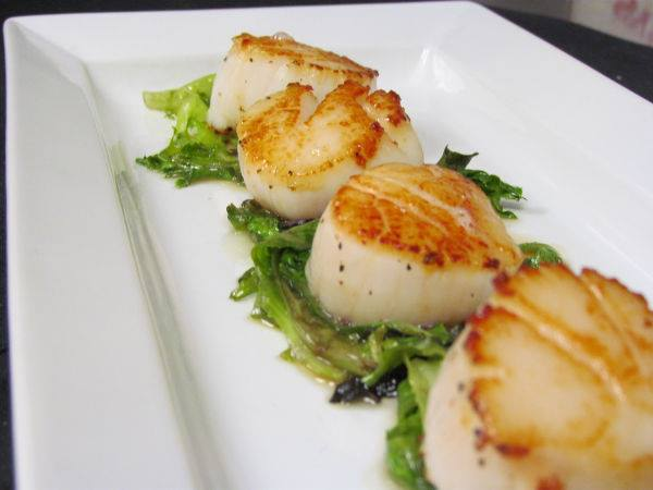 Seared Scallops - Fresh sea scallops sauteed to perfection, served atop wilted greens and drizzled with our scrumptious house made orange caramel reduction.