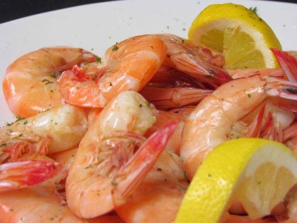 Close up image of shrimp uncooked with lemon slices.