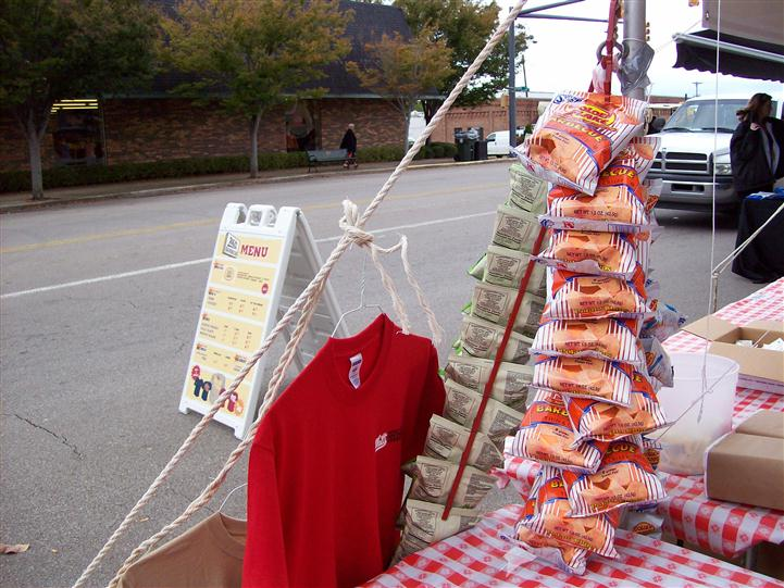 t-shirts hung on a rope, with an array of chip bags hung on a rope