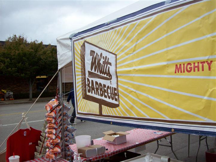 sign on the barbeque tent, displaying the Whitts Barbeque logo