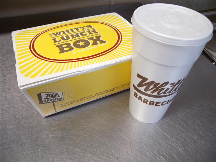 "Whitts Lunch Box, beside a styrofoam cup labelled ""Whitt's Barbeque"""