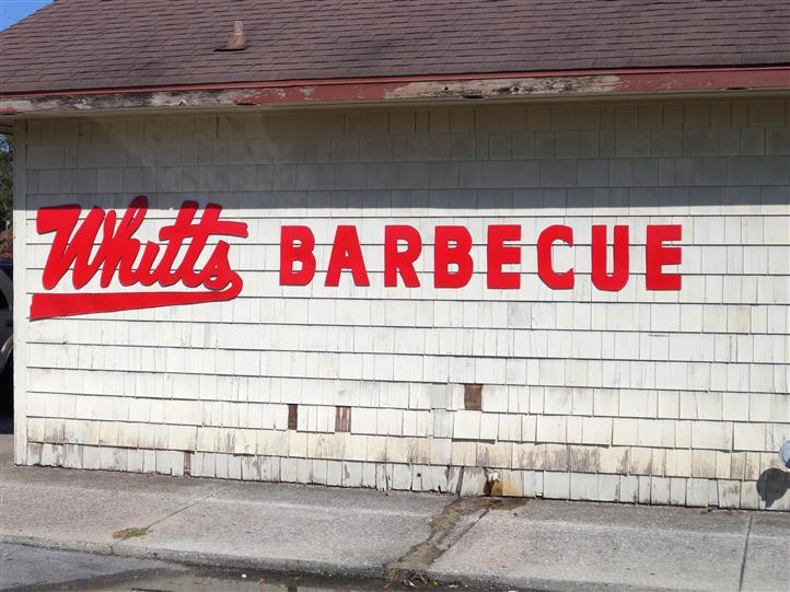 "side of store, with ""Whitts Barbeque"" written on a mural"